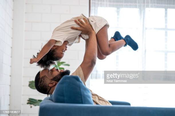 african father picking up daughter in the air, face to face. they are having fun in weekend at home. - life insurance stock pictures, royalty-free photos & images
