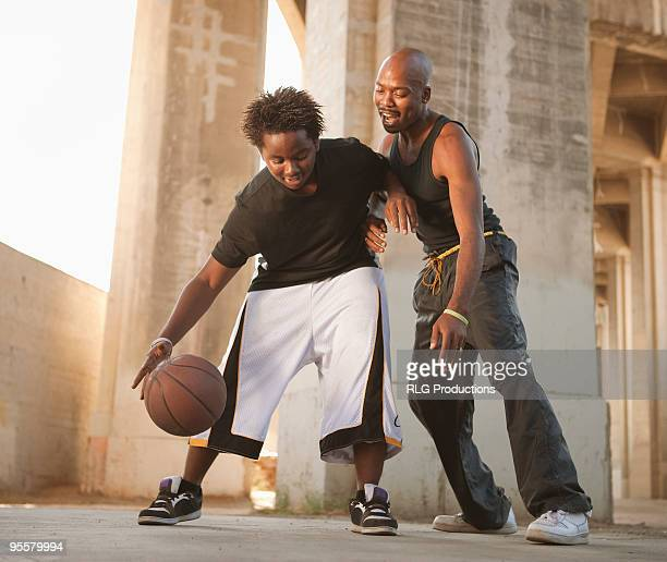 African father playing basketball with son
