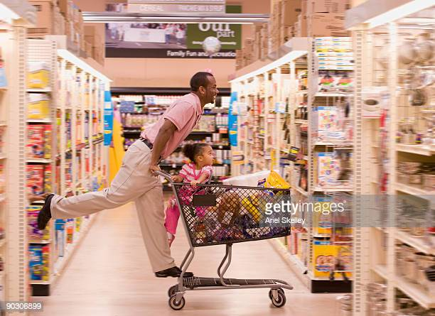 african father pushing daughter in grocery cart - shopping cart stock pictures, royalty-free photos & images