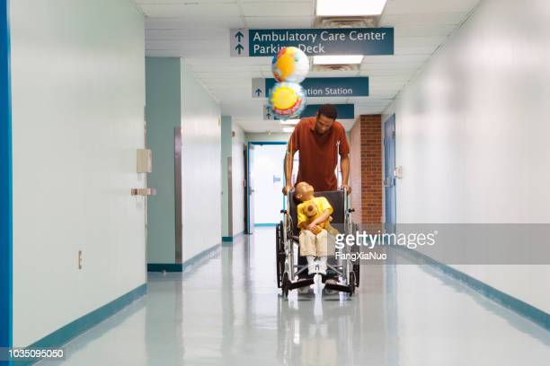 african father pushing son in wheelchair down hospital corridor - leaving stock pictures, royalty-free photos & images