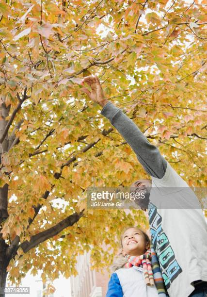African father showing tree to daughter