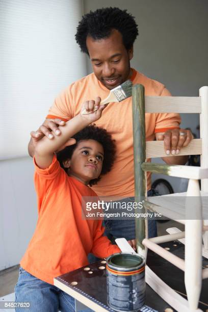 African father teaching son to paint rocking chair
