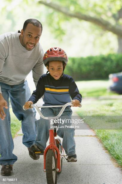 African father teaching son to ride bicycle