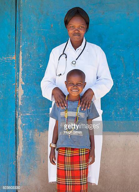 african female doctor and smiling girl (10-12) standing against blue wall - hugh sitton bildbanksfoton och bilder