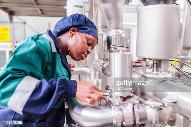 african female factory worker checking the gauge - labor day stock pictures, royalty-free photos & images