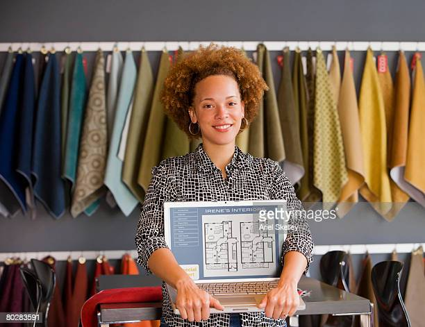 african female interior designer holding laptop - interior design foto e immagini stock