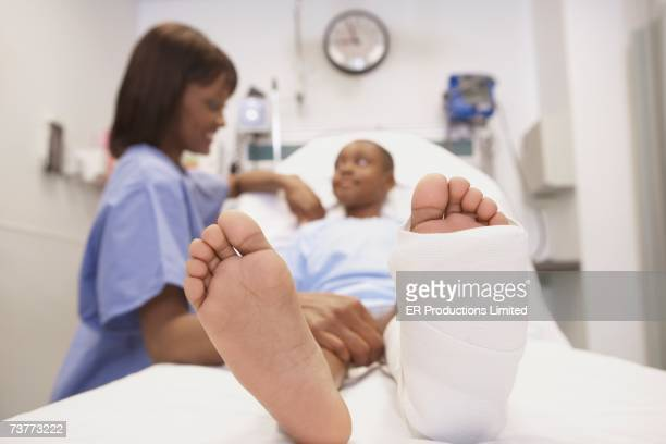 African female nurse smiling at African boy with broken leg in hospital bed