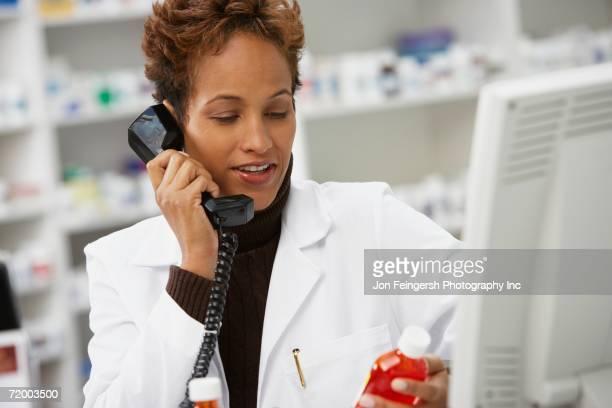 African female pharmacist holding medication and using telephone