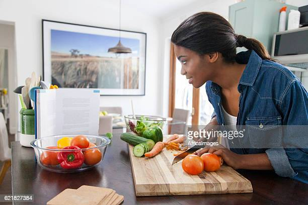 African female reading from a cookbook while chopping carrots.