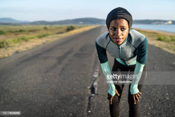 african female runner with hijab - muslim woman beach stock photos and pictures