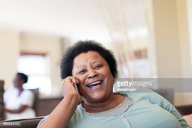 African female senior laughing on the phone.
