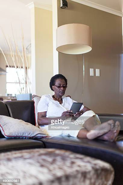 Femme d'Afrique senior lire un message sur son ordinateur
