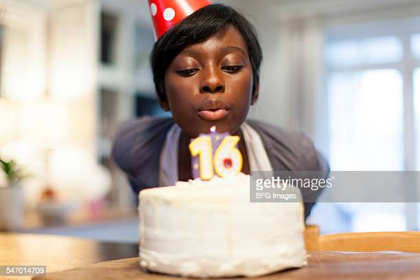 African female teenager blowing out the candle on her 16th birthday cake , Cape Town, South Africa