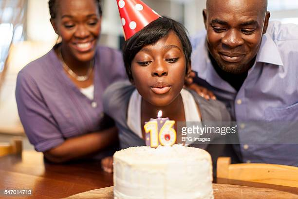 African female teenager blowing out the candles on her 16th birthday cake, surrounded by her family , Cape Town, South Africa