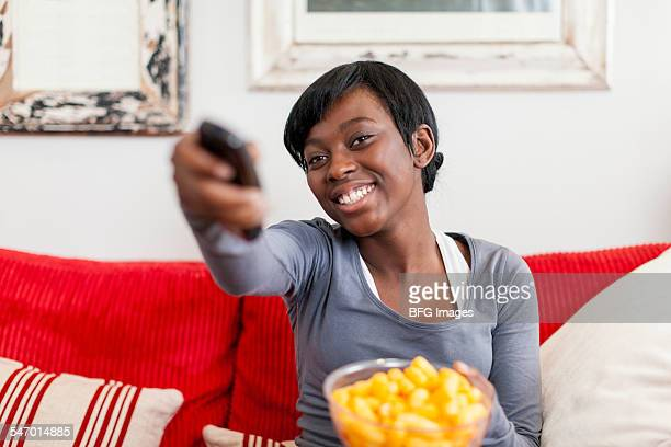 African female teenager sitting on sofa changing the television channel, holding a bowl of crisps , Cape Town, South Africa