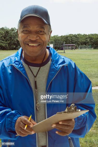 African football coach holding clipboard on field