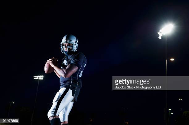 african football player throwing football - quarterback stock-fotos und bilder