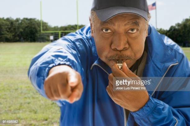 African football referee blowing whistle