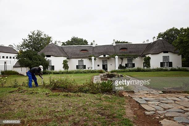 African gardener at work in large Swellendam house garden