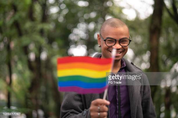 african gay man waving rainbow flag - lgbtq stock pictures, royalty-free photos & images