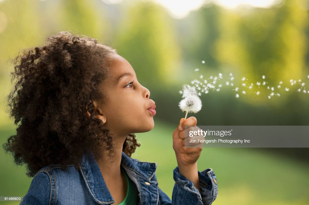 African girl blowing dandelion seeds : Stock Photo