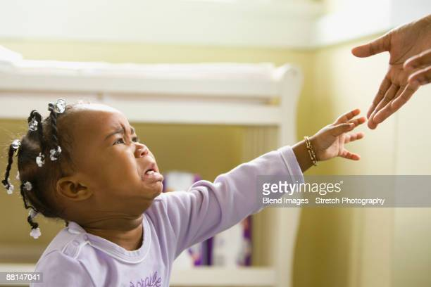 African girl crying and reaching upward