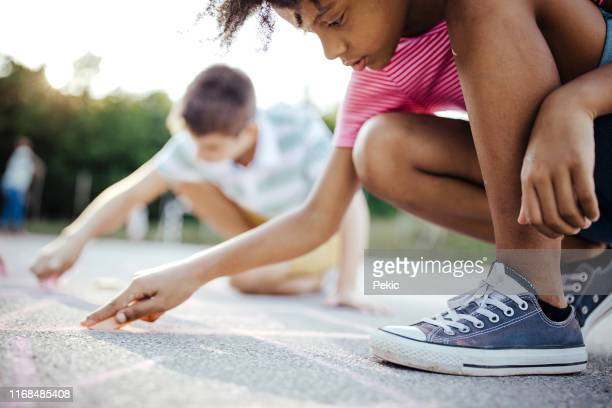 african girl drawing hopscotch on asphalt with friends - chalk drawing stock pictures, royalty-free photos & images