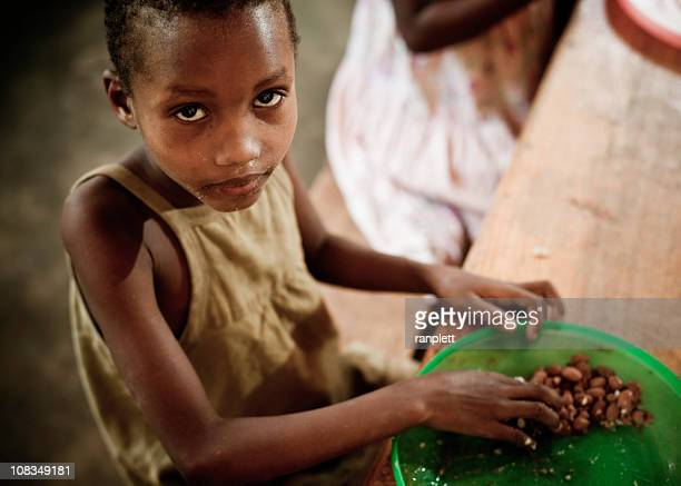 african girl eating a meal in the orphanage - armoede stockfoto's en -beelden
