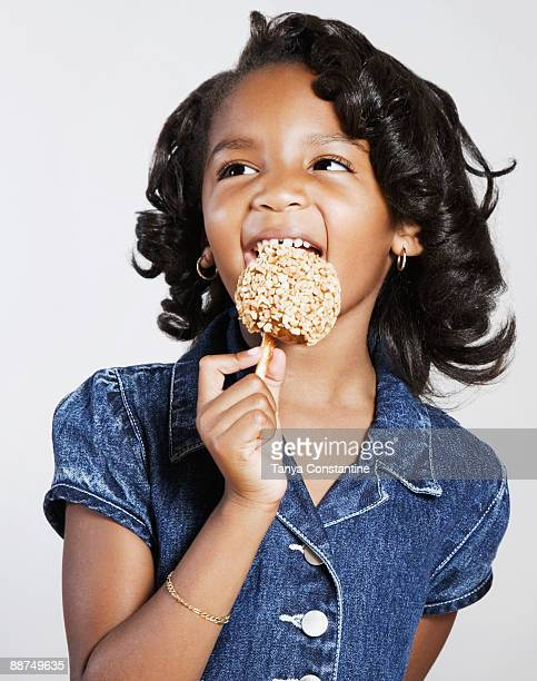 african girl eating candy apple - 噛む ストックフォトと画像