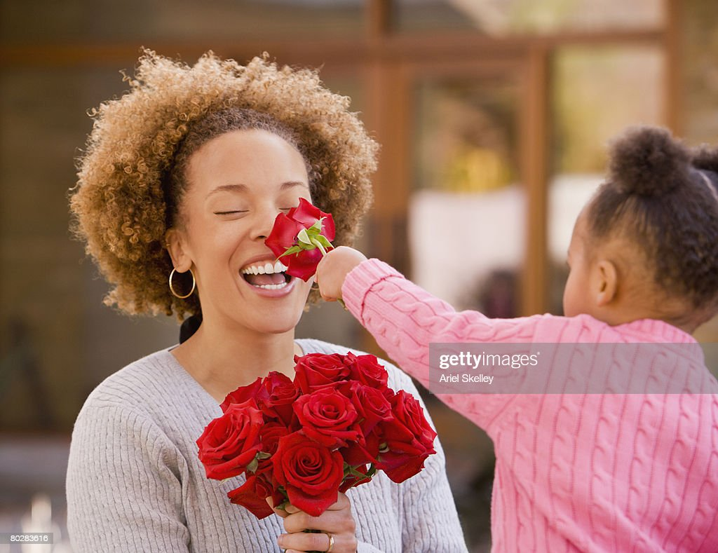 African girl giving flowers to mother : Stock Photo