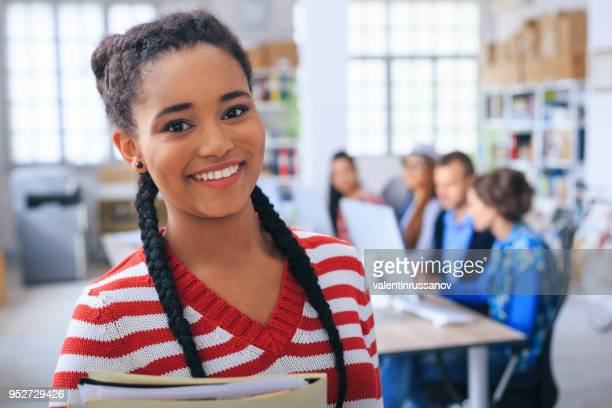 African girl holding documents, looking at camera