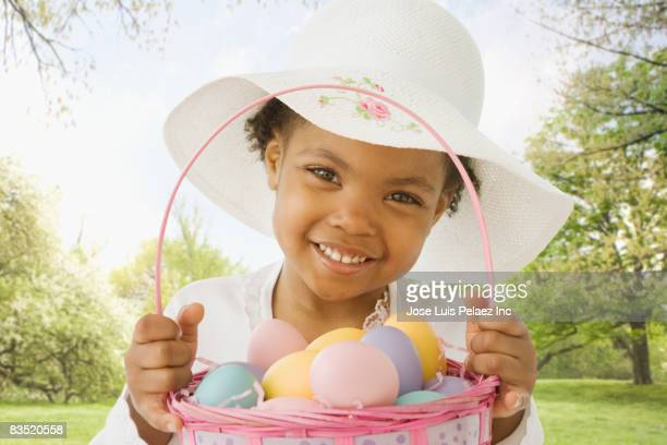 African girl holding Easter basket of eggs