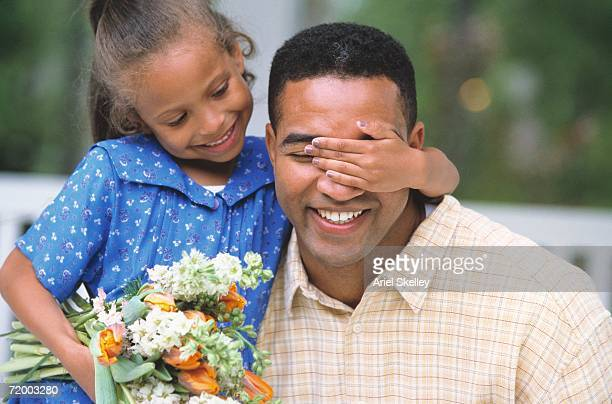African girl holding flowers and covering father's eyes