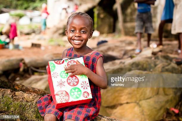 Fille africaine tenant un sac-cadeau