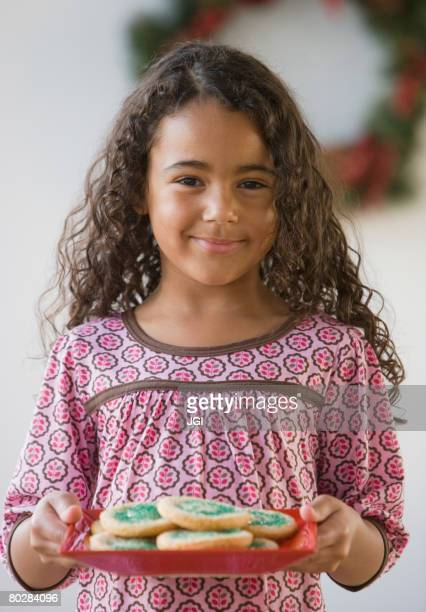 African girl holding plate of cookies
