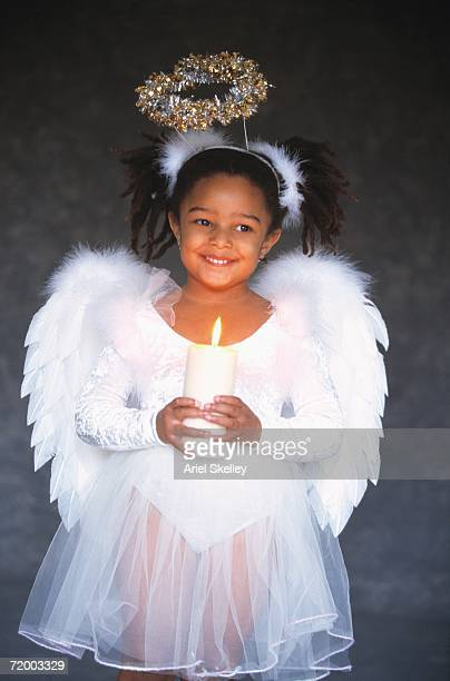 African girl in angel costume holding candle