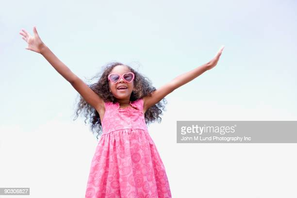 African girl in sunglasses with arms outstretched
