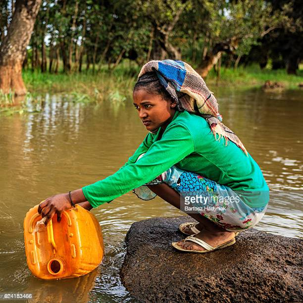 African girl is taking water from the river, Ethiopia, Africa