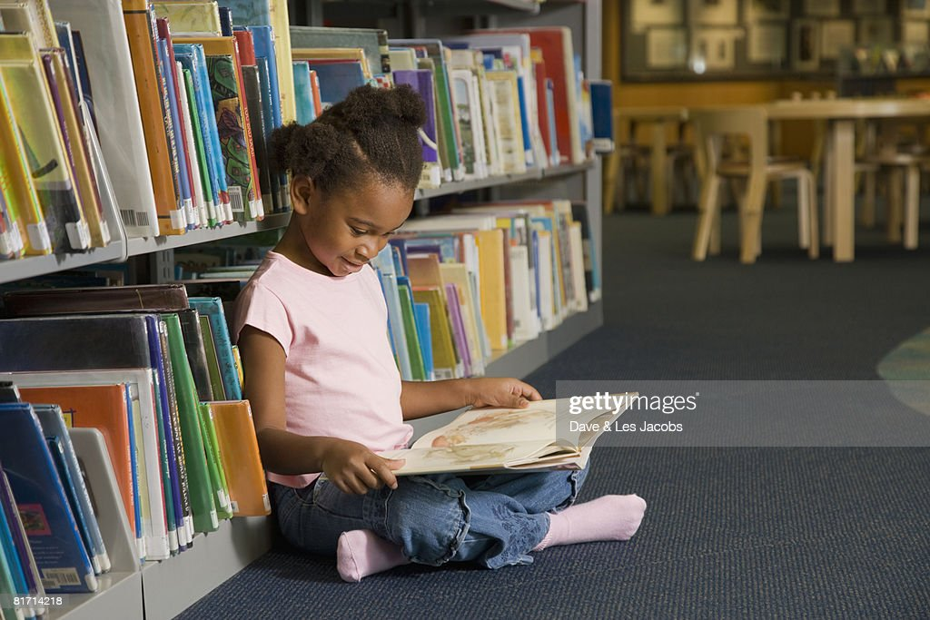 African girl reading library book : Stock Photo