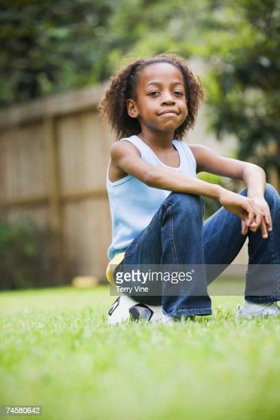African girl sitting on soccer ball