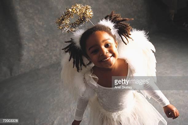 african girl smiling in angel costume - christkind stock-fotos und bilder