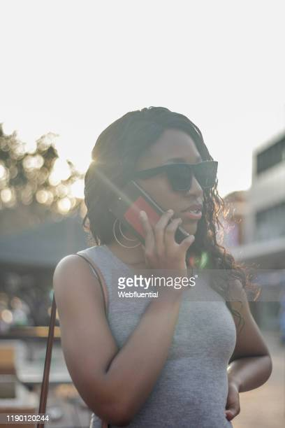 african girl speaking on the phone - webfluential stock pictures, royalty-free photos & images
