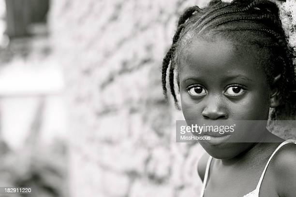 African girl standing against a brick wall