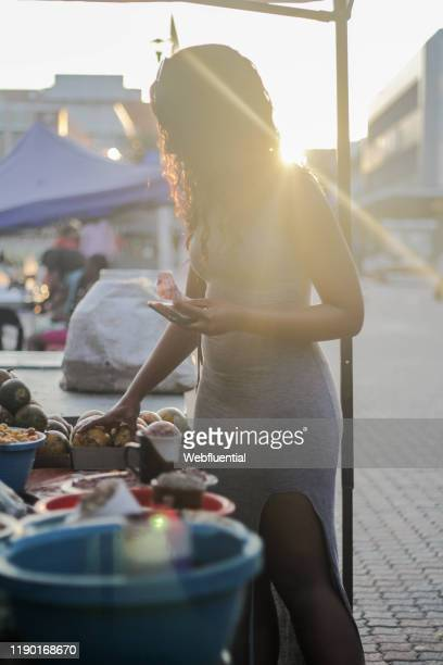 african girl standing in a market holding a smartphone - webfluential stock pictures, royalty-free photos & images