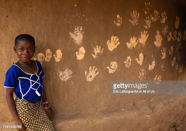 African girl standing in front of handprints on the wall of a hut Bafing Gboni Ivory Coast on May 5 2019 in Gboni Ivory Coast