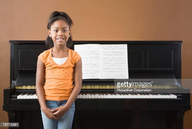 African girl standing in front on piano