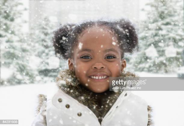 African girl standing outdoors in falling snow