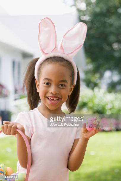 African girl wearing bunny ears and holding Easter egg