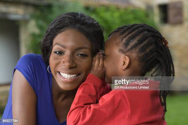 African girl whispering to mother