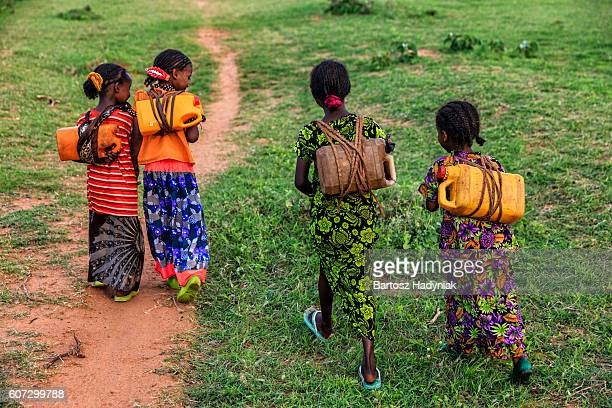 african girls carrying water from the well, ethiopia, africa - carrying stock pictures, royalty-free photos & images